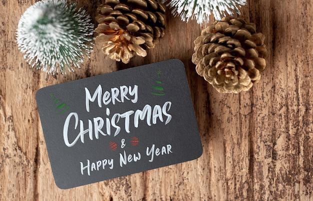 Vista superior do feliz natal e feliz ano novo no quadro-negro com árvore de natal e pinha