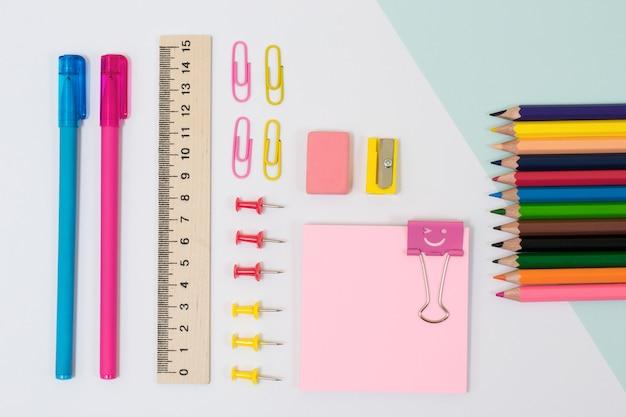 Vista superior do fichário de alfinetes de clipes de adesivos com desenho de sorriso de cor apontador de lápis borracha canetas e régua azul e rosa