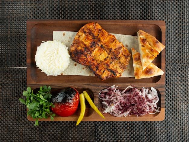 Vista superior do filé de frango grelhado servido com cebola e legumes de pão de arroz