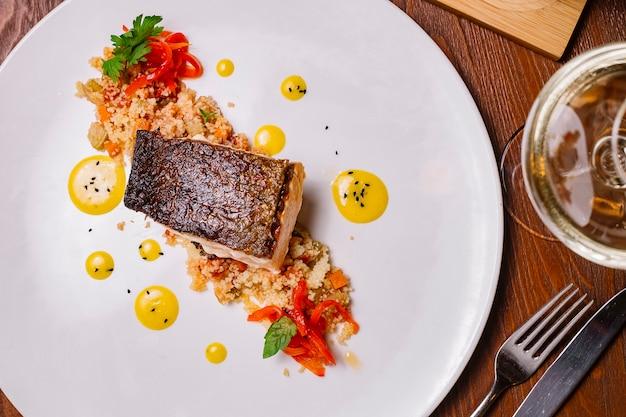 Vista superior do filé de peixe grelhado servido em cima da salada de cuscuz com pimentão