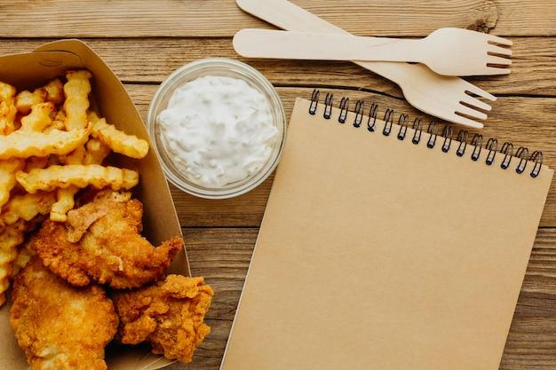 Vista superior do fish and chips com notebook e garfos