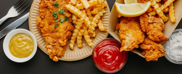Vista superior do fish and chips com seleção de molhos e talheres