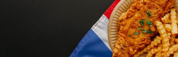 Vista superior do fish and chips no prato com a bandeira da grã-bretanha e copie o espaço