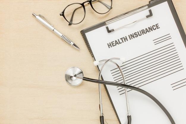 Vista superior do formulário de seguro de saúde e óculos com estetoscópio no fundo de madeira. conceito de negócios e cuidados de saúde.savings.flat lay.copy space.