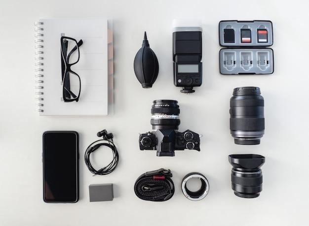 Vista superior do fotógrafo de espaço de trabalho com câmera digital, flash, kit de limpeza
