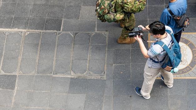 Vista superior do fotógrafo homem usa a câmera e fica na rua de pedestres ao ar livre