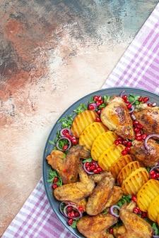 Vista superior do frango - as apetitosas asas de frango com batatas na toalha de mesa quadriculada