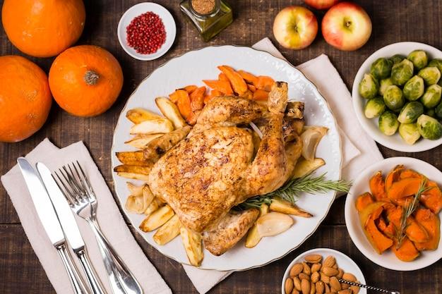 Vista superior do frango assado de ação de graças com talheres e outros ingredientes
