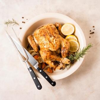 Vista superior do frango assado no dia de ação de graças com rodelas de limão e talheres