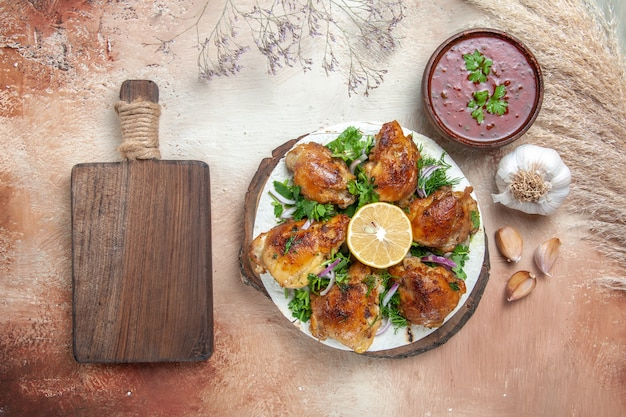 Vista superior do frango com molho de ervas e limão e alho ao lado da tábua de corte