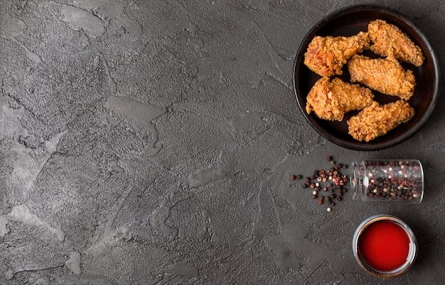 Vista superior do frango frito com pimenta, molho e cópia-espaço