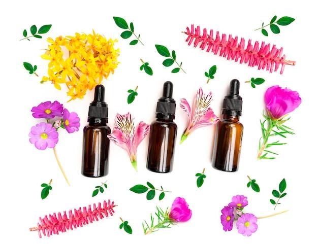 Vista superior do frasco conta-gotas de óleo essencial de aroma entre flores coloridas