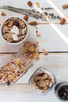 Vista superior do frasco de granola derramado perto de flocos de milho; frutas secas e pedaços de chocolate na superfície de madeira
