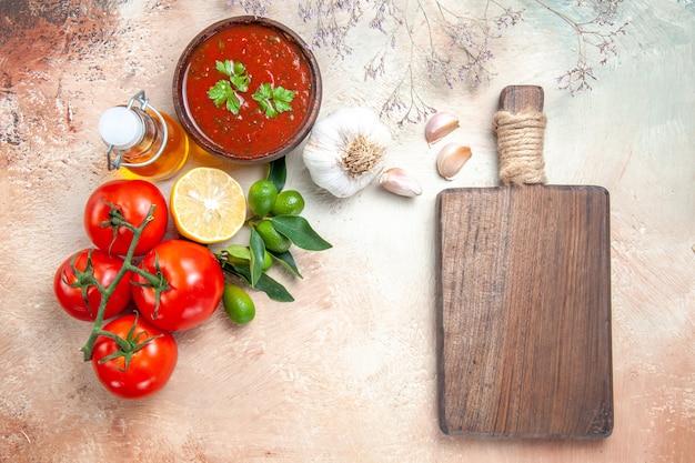 Vista superior do frasco de molho de tomate com óleo e pedicelos, molho de limão e alho, a tábua de corte