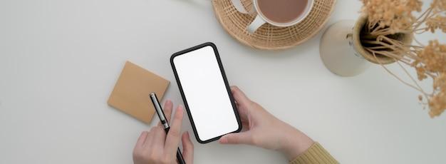 Vista superior do freelancer feminino usando smartphone mock-up para entrar em contato com o cliente na mesa branca