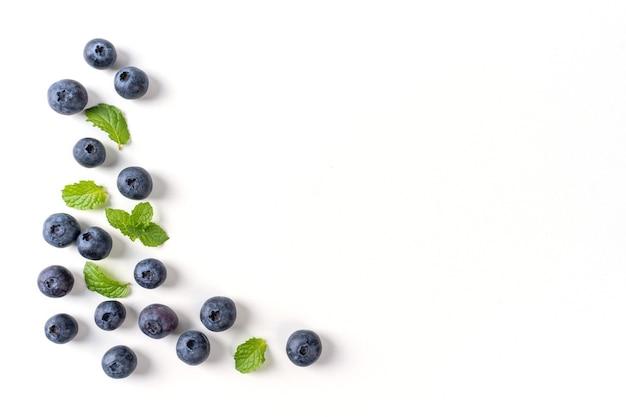 Vista superior do fruto do mirtilo isolada em um fundo branco, layout aéreo plano leigo com folha de hortelã, conceito de design saudável.