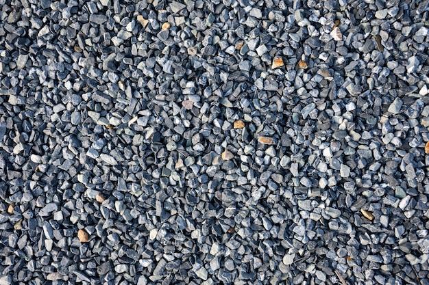 Vista superior do fundo azul da textura do cascalho da construção. fundo de quadro completo de pedra de granito pequeno.
