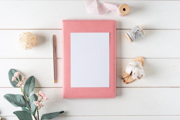 Vista superior do fundo branco da mesa de trabalho com caderno de papel em branco, algodão natural. postura plana
