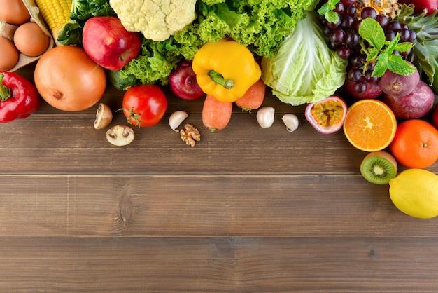 Vista superior do fundo da bancada da cozinha de madeira alimentos saudáveis e crus mistos coloridos