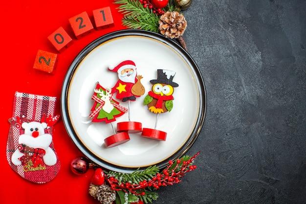 Vista superior do fundo de ano novo com acessórios de decoração de prato de jantar ramos de abeto e números de meia de natal em um guardanapo vermelho sobre uma mesa preta