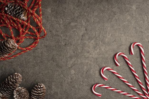 Vista superior do fundo de natal com bastões de doces e pinhas