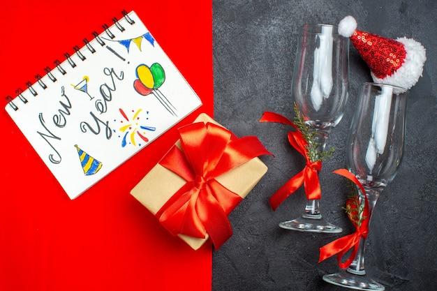 Vista superior do fundo de natal com o caderno de taças de vidro de chapéu de papai noel com a escrita de ano novo, desenhos e presentes em fundo vermelho e preto