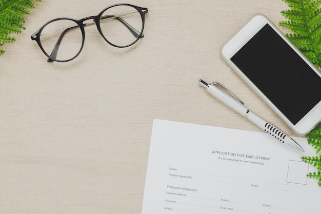 Vista superior do fundo do escritório do escritório de negócios. a aplicação para um formulário de trabalho e lápis lápis, o telefone móvel da árvore dos óculos no fundo da mesa de madeira com espaço da cópia.
