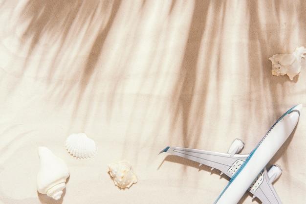Vista superior do fundo do viajante na areia tropical, conchas e avião.