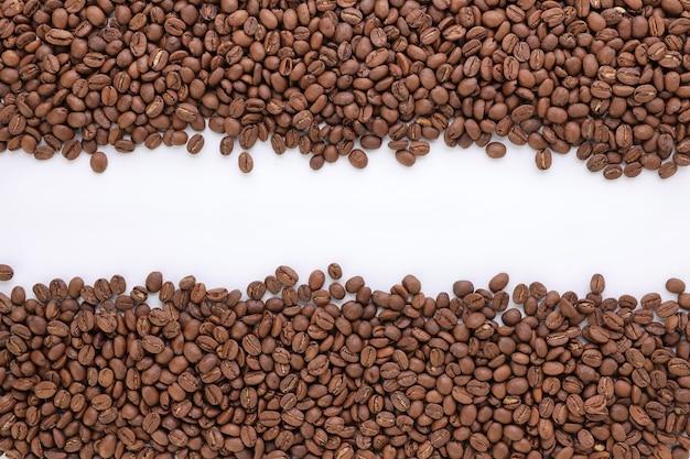 Vista superior do fundo dos grãos de café recém-torrados, isolada no fundo branco