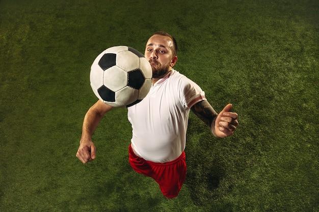 Vista superior do futebol caucasiano ou jogador de futebol sobre fundo verde de grama. jovem modelo desportivo masculino treinando, praticando. chutando a bola, atacando, pegando. conceito de esporte, competição, vitória.