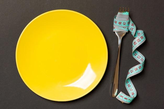 Vista superior do garfo com fita métrica perto de prato redondo no preto. perda de peso com espaço vazio para a sua ideia