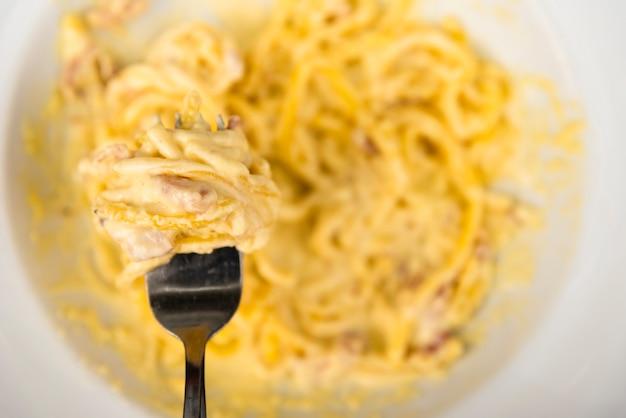 Vista superior do garfo com macarrão espaguete de queijo