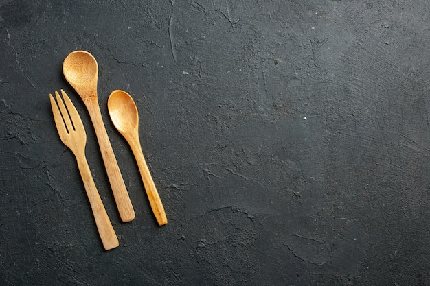 Vista superior do garfo e colheres de madeira na mesa escura com espaço livre