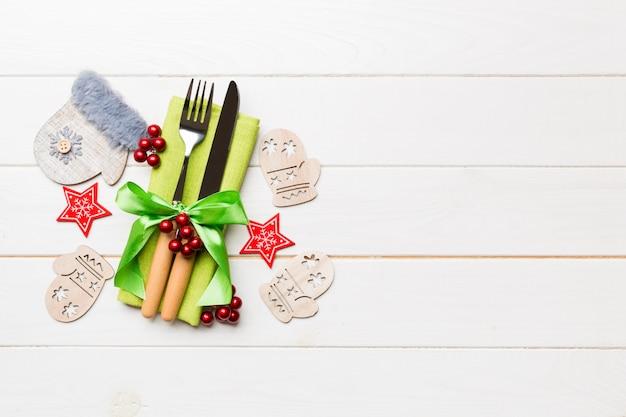Vista superior do garfo e faca no guardanapo com fundo de madeira. diferentes decorações de natal e brinquedos. conceito de jantar de ano novo com espaço vazio