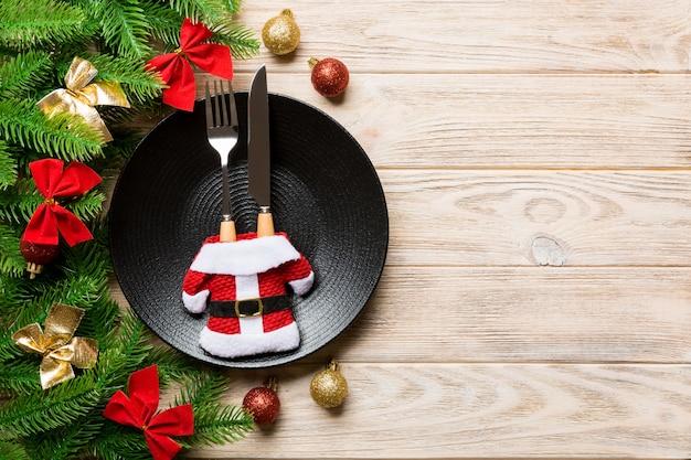 Vista superior do garfo, faca e prato cercado com abeto e decoração de natal na superfície de madeira