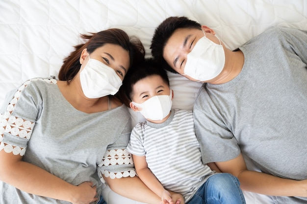 Vista superior do garotinho fofo e seus pais asiáticos olhando para a câmera e usando máscara