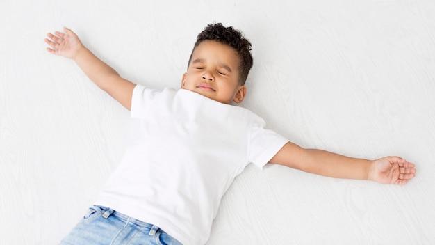 Vista superior do garoto posando com braços abertos