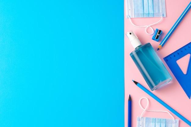 Vista superior do gel desinfetante para as mãos e material escolar
