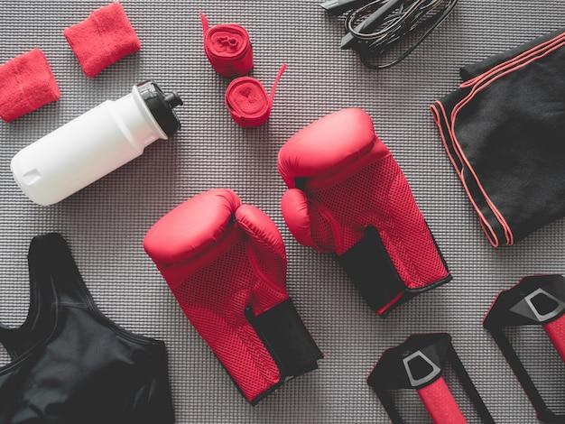 Vista superior do ginásio de boxe com luva de boxe, roupa de ginástica, pular corda e acessórios
