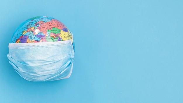 Vista superior do globo usando máscara médica com espaço de cópia
