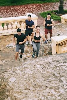 Vista superior do grupo de adolescentes malhando juntos correndo lá em cima