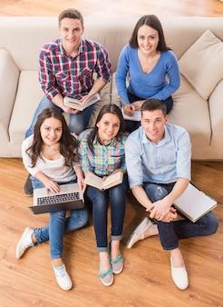 Vista superior do grupo de estudantes estão sentados no sofá.