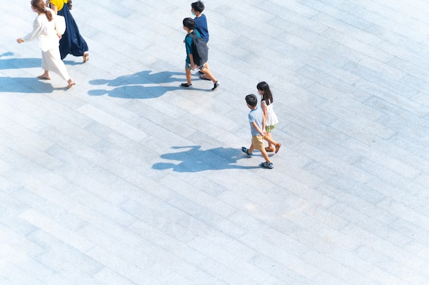 Vista superior do grupo de mães e crianças caminhando na passarela de pedestres ao ar livre para viajar