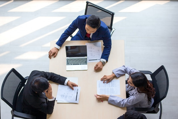 Vista superior do grupo de pessoas ocupadas multiétnicas, trabalhando em um escritório, vista aérea com o empresário e a empresária sentado em torno de uma mesa de conferência com espaço em branco da cópia, reunião de negócios