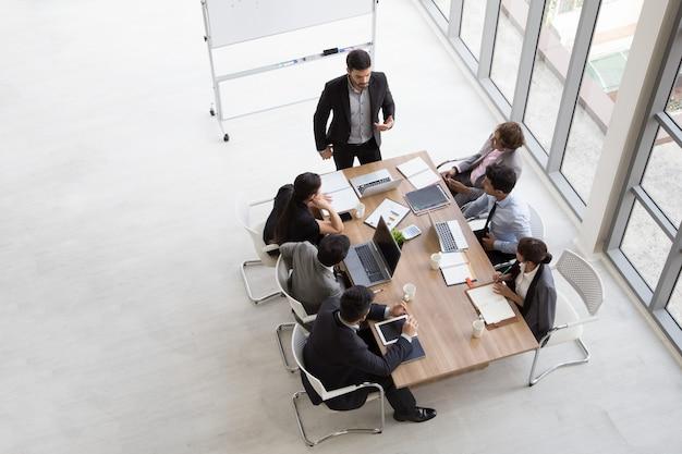 Vista superior do grupo de pessoas ocupadas multiétnicas, trabalhando em um escritório