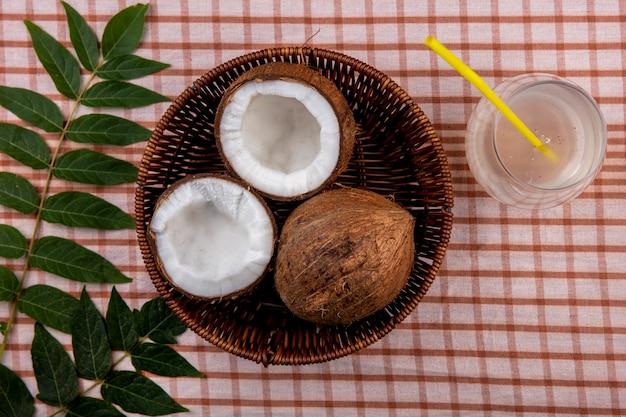 Vista superior do haf e coco inteiro em um balde com folhas na superfície da toalha de mesa marcada