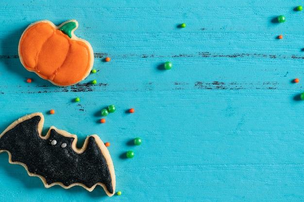 Vista superior do halloween festivo decorado biscoitos de açúcar de gengibre em fundo azul com espaço de cópia e plana leigos.