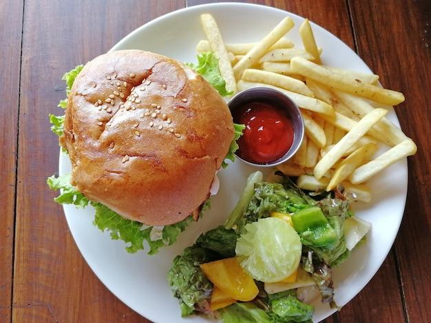 Vista superior do hambúrguer em um prato com um prato de batatas fritas e salada fresca, além de ketchup