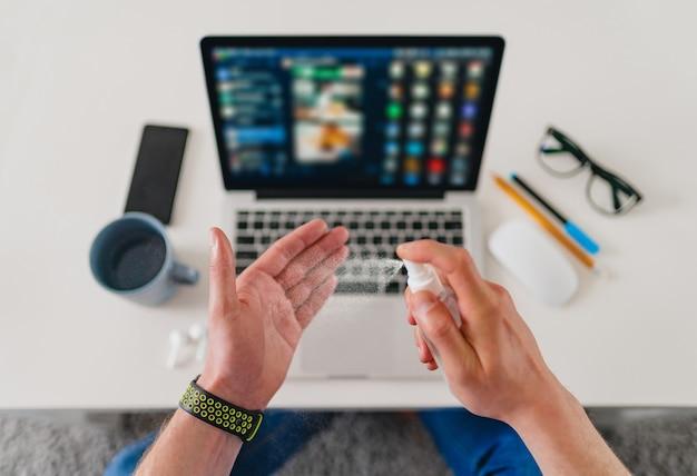 Vista superior do homem, close-up da mesa, limpando as mãos com spray anti-séptico desinfetante no local de trabalho em casa trabalhando no laptop