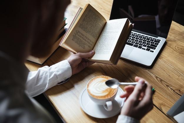 Vista superior do homem de camisa branca, mexendo o café durante a leitura do livro